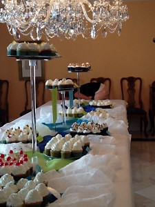 a cupcake table filled with delicious cake and icing